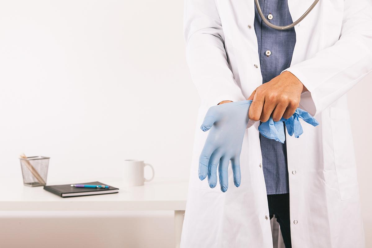 Ginekolog se sprema na pregled ili na intervenciju kod pacijentkinje, pa stavlja hirurške rukavice na ruke. Obučen je u beli mantil.