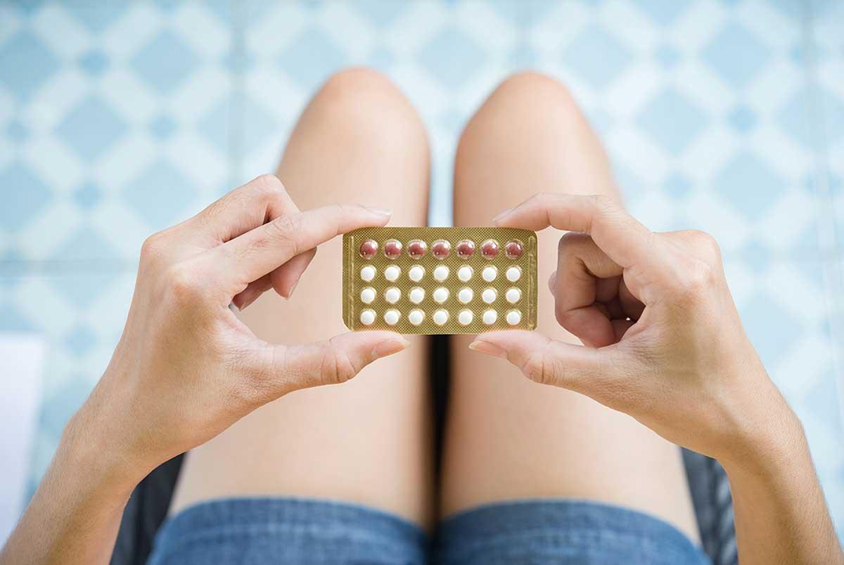 Devojka u rukama drži sredstva za kontracepciju - bebi pilule.
