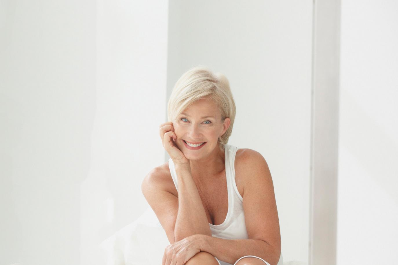 Žena u menopauzi koja se smeje i deluje srećno i zadovoljna. Sedi u svojoj kući, lice joj je naslonjeno na ruku.