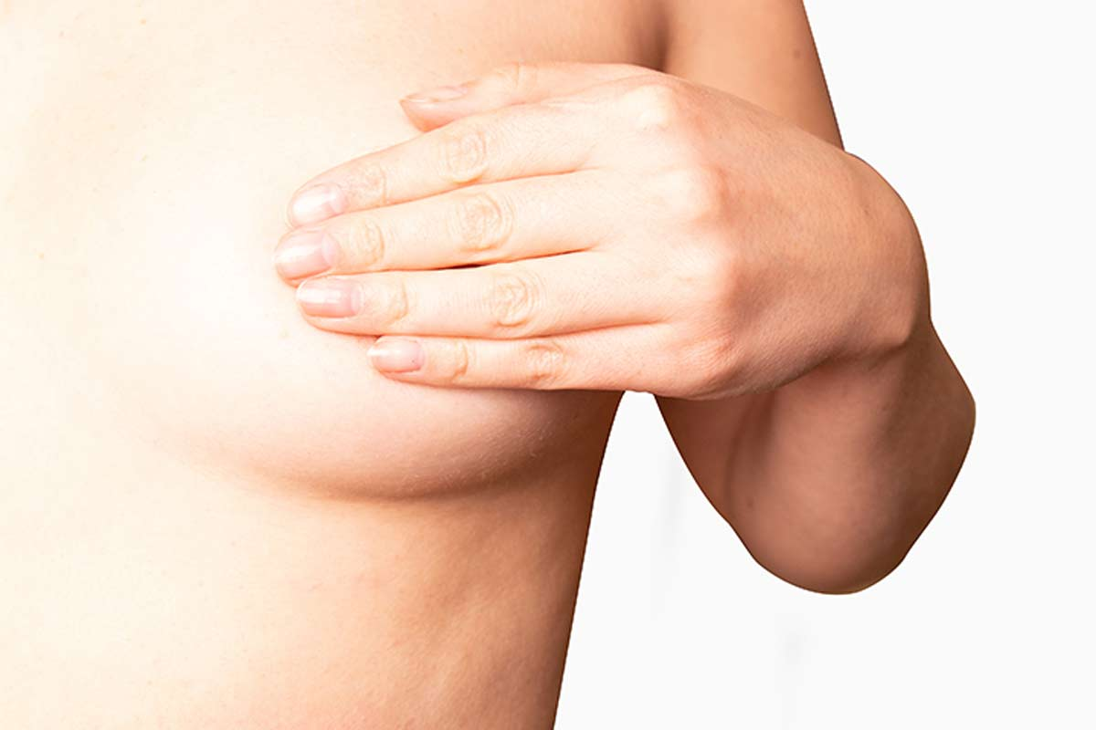 Žena levom rukom prekriva levu dojku, kao da proverava da li je boli i da li je nešto čudno kad je u pitanju njen oblik.