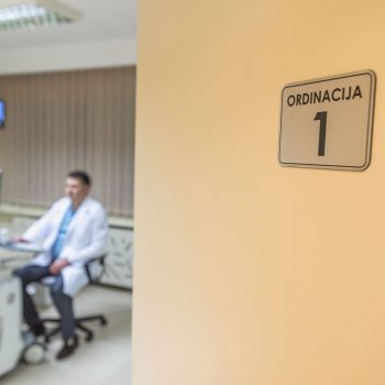 Fotografija vrata Ordinacije broj 1 Ginekologije Tiršova. U bluru, u pozadini, vidi se doktor Aleksandar Dobrosavljević koji koristi 4d ultrazvučni aparat.